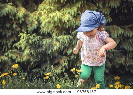 Carefree childhood with playful cheerful child girl running  on meadow  among trees and flowers during summer holidays