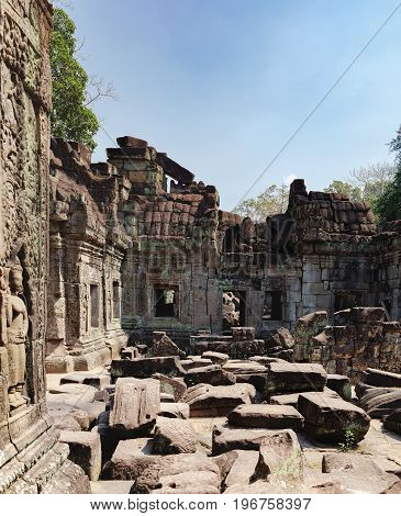 The ancient ruins of the Preah Khan Temple in Siem Reap, Cambodia. View from a window on piles of stones and temple walls. Ancient Khmer architecture, famous Cambodian landmark, World Heritage