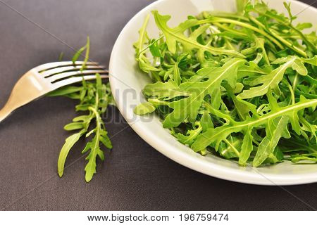 fresh green arugula salad on a ceramic plate pinned on a fork dark tablecloth background