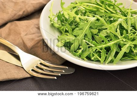 fresh green arugula salad on ceramic plate with steel fork and knife dark tablecloth background healthy food concept