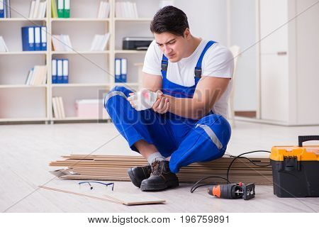 Young worker working on floor laminate tiles