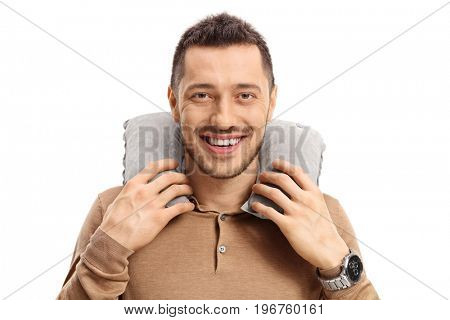 Young man with a neck pillow looking at the camera and smiling isolated on white background