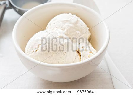 Vanilla ice cream scoops in white bowl