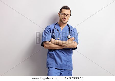 Doctor with his arms crossed leaning against a wall