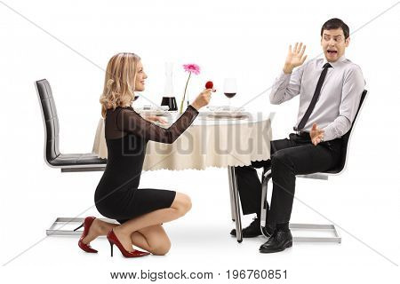 Young woman proposing to her shocked boyfriend at a restaurant table isolated on white background