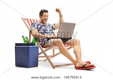 Joyful tourist with a laptop sitting in a deck chair next to a cooling box with bottles of beer isolated on white background