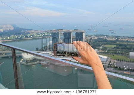 Woman hand takes a photo on her smart phone
