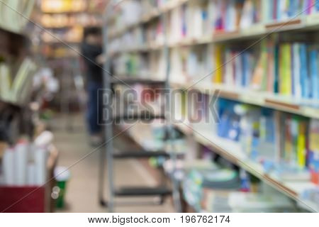 Blurred bookshelves in book store or in library. In the background a woman chooses a necessary book. Education concept, reading fiction