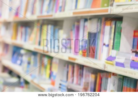 Blurred school library bookshelf with colorful book, smanuals and textbooks. Education, school, study concept. Abstract background