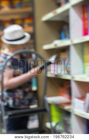 Blurred bookshelves in book store or in library. Woman chooses a necessary book. Education concept, reading fiction, pension, interests in the elderly, life style