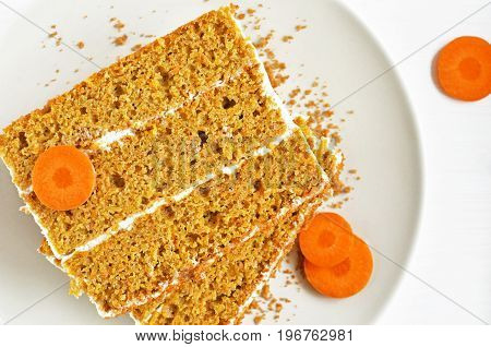 sweet carrot cake dessert slices with cream from sour cream over white wooden background top view