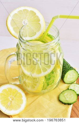 detox water with cucumber and lime in retro glass jar on yellow textile napkin background healthy lifestyle concept