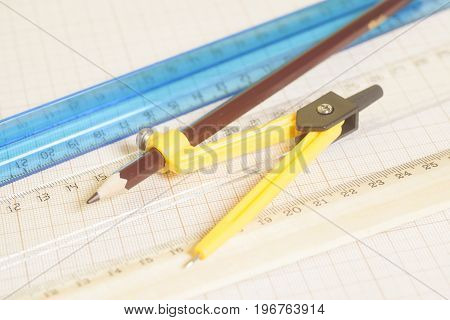 Yellow Drawing Compass With Pensil  And Rulers On Graph Paper.engineering Concept.