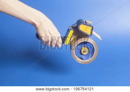 Woman holding an industrial tape dispenser .