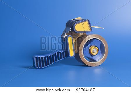 Industrial Tape Dispenser On A Blue Background