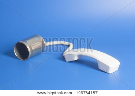 Tin Can Phone With Handset On Blue Background