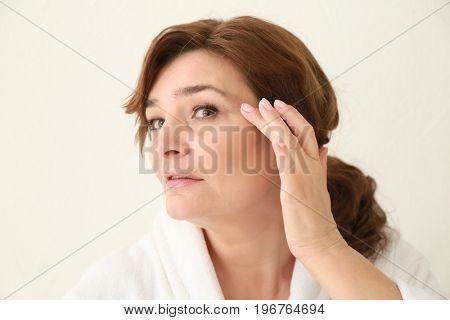 Beautiful elderly woman posing on light background