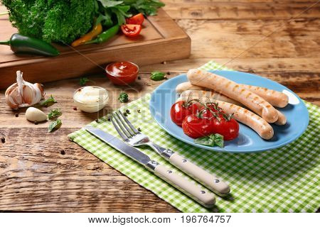 Plate with roasted sausages and tomatoes on wooden background