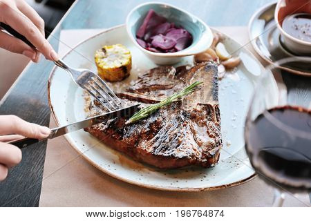 Woman's hands cutting tasty beefsteak on white plate with fork and knife on wooden table