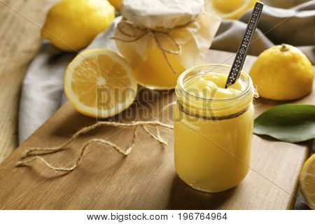 Glass jar with delicious lemon curd on wooden board