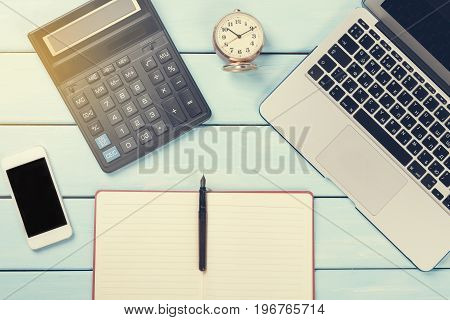 Business concept. Working desk with Laptop fountain pen Calculator Alarm Clock phone and notebook on wooden table. Toned