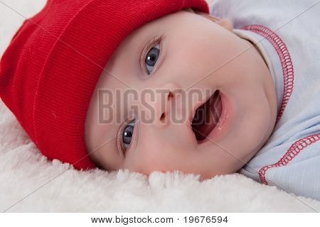 Adorable Baby Boy Lying Smiling With Red Hat On