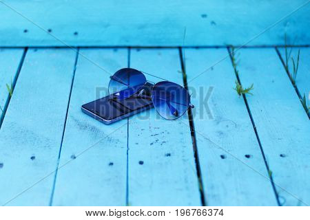 Sunglasses and smartphone phone on blue boards