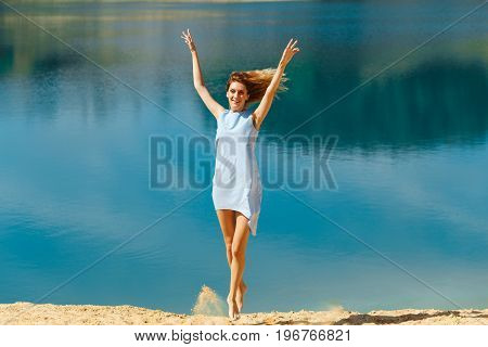 Young Woman In A Blue Dress Jumping On The Beach