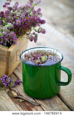 Enameled Mug Of Thyme Healing Herbs And Wooden Box Full Of Thymus Serpyllum For Healthy Herbal Tea.