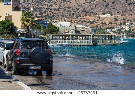 Elounda Crete Greece 22 September 2013: Cars are parked on a narrow path along the water's edge of the Mirabello Bay.
