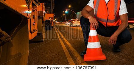 Repairing the road in the night city. Working man sitting.