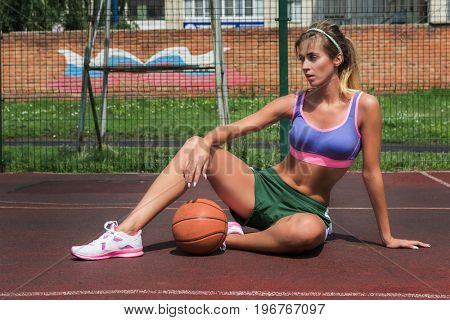 A young beauty athletic woman in sportswear with basketball ball. Russian flag on background