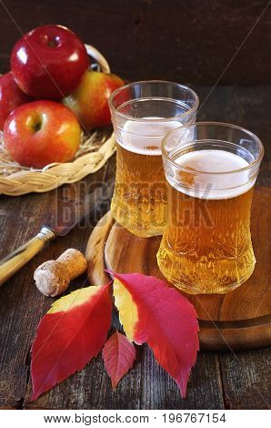 Two glasses of apple cider and red apples in wicker basket. Rustic style