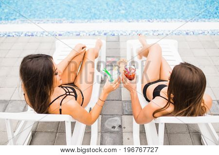 Girlfriends Clinking Glasses With Cocktails At Lounge At The Poolside In Summer