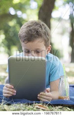 Little Cute Boy Lying On The Grass And Looking Carefully At His Tablet