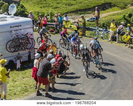 Col du Grand ColombierFrance - July 17 2016: Group of cyclists riding in a hairpin curve at Col du Grand Colombier in Jura Mountains during the stage 15 of Tour de France 2016.