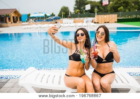 Two Attractive Brunette Women Wearing Bikini Posing Near The Swimming Pool, Making Selfie Photo. Sum