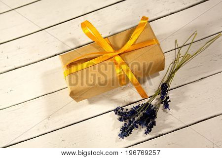 Gift festive box with lavender flowers and yellow ribbon on white wooden rustic background. Soft selective focus.