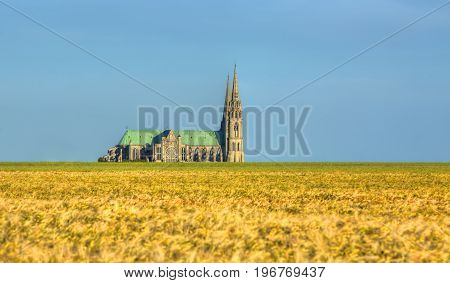 Image of the Cathedral of Our Lady of Chartres seen from outside of the city above the fields of cereals which surround the locality.This is a very famous Gothic cathedral which contains original stained glass from the 13th century.
