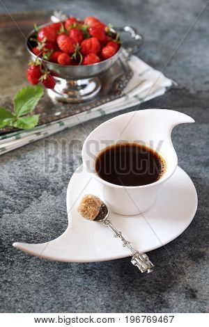 Wild strawberries and cup of black coffee on dark background