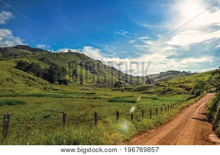 View of rural road next to green hills near the town of Joanópolis. In the countryside of São Paulo State, a region rich in agricultural and livestock products, southwestern Brazil. Retouched photo