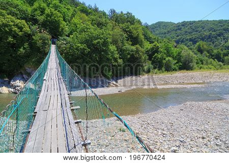 View of walking suspension bridge and mountain river of right