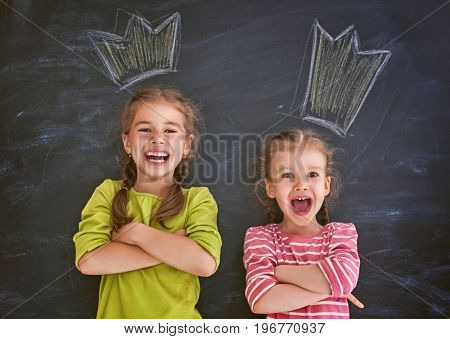 Funny children on a background of black board. Girls are having fun and drawing crowns. Concept of successful education.