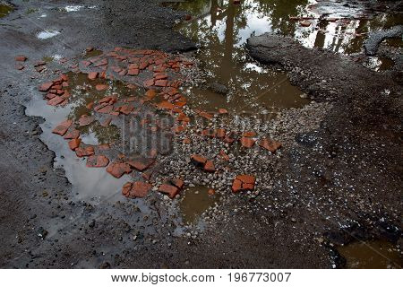 Photo of a large road pit on asphalt pavement