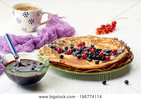 Thin pancakes stack with blueberries and red currant jam on white wooden table