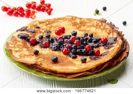 Thin pancakes stack with fresh summer berries on white wooden table