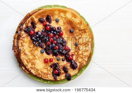 Thin pancakes with fresh summer berries on white wooden table. Top view with space for text