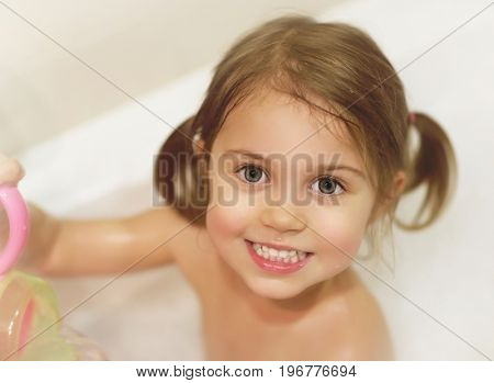Photo of cute baby girl taking bath, happy childhood, child's hygiene, healthy adorable kid, sweet infant in bathroom, pretty toddler having fun in bathtub, baby's soap and shampoo, healthcare concept