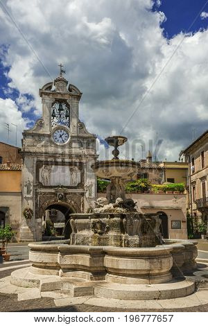 Sutri main square in the historic city center with fountain old clock tower and clouds