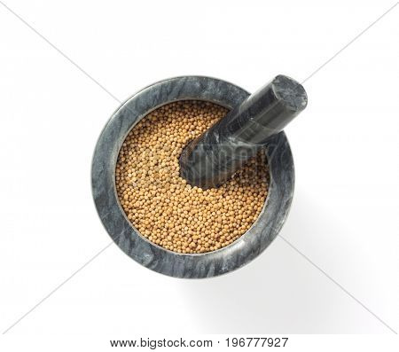 mustard seeds in mortar isolated on white background